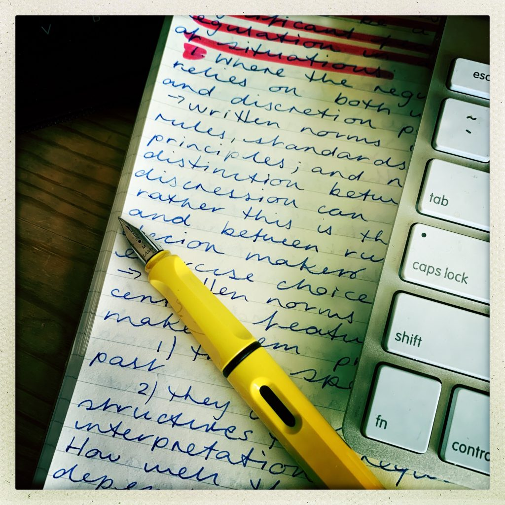 A yellow fountain pen is on top of some handwritten work. Keyboard nearby